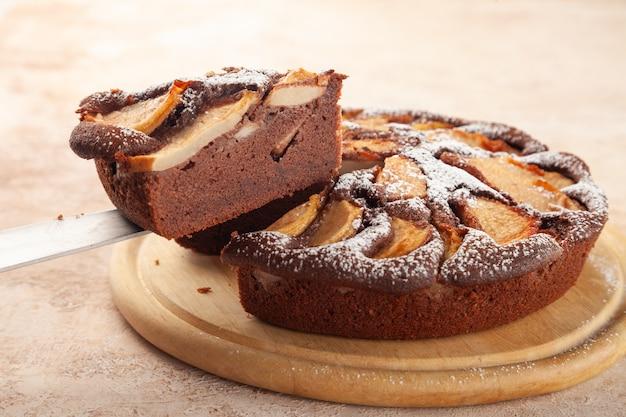 Torta fatta in casa con cioccolato, mele, fetta di torta tagliata sul coltello, piatto di legno, spazio copia, posto per testo, vista laterale, close-up