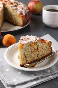 Torta fatta in casa con semi di papavero, albicocche e mele con una tazza di caffè su sfondo grigio. disposizione verticale. avvicinamento