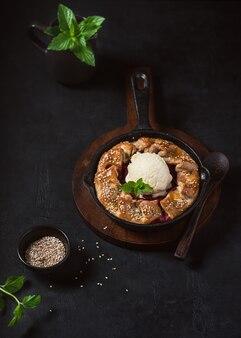 Torta fatta in casa con fragole, gelato alla vaniglia e semi di sesamo nel tavolo rustico scuro.