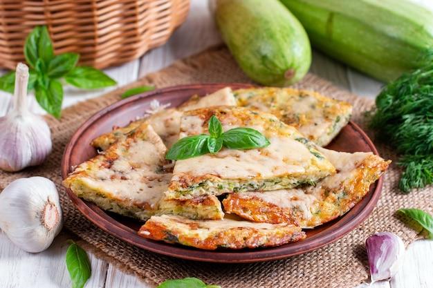 Torta fatta in casa con zucchine, formaggio ed erbe aromatiche sul tavolo