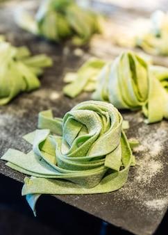 Mucchi fatti in casa di fettuccine di spinaci freschi che spolverizzano la farina per tenerli lontani