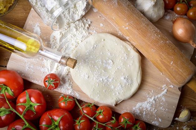 Pasta per pizza fatta in casa con cipolle e pomodori freschi