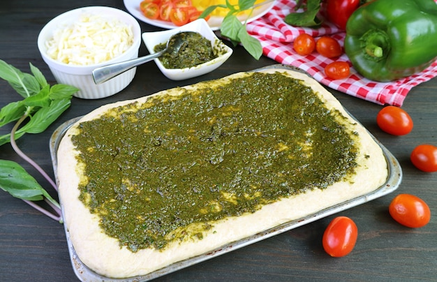 Impasto per pizza fatto in casa con salsa al pesto prima di infornare in una cucina disordinata