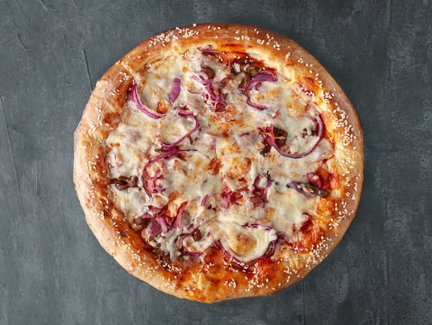 Pizza fatta in casa con salsiccia di caccia, cipolle rosse sott'aceto, funghi, mozzarella e salsa di pomodoro. lato largo. vista dall'alto. su uno sfondo di cemento grigio. isolato.