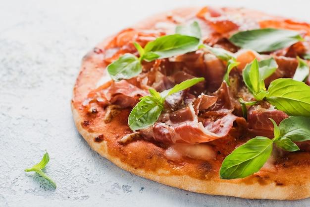 Pizza fatta in casa con prosciutto, mozzarella e foglie di basilico fresco su una vecchia superficie di cemento leggero