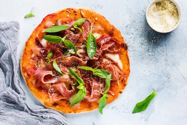 Pizza fatta in casa con prosciutto, mozzarella e foglie di basilico fresco su un vecchio cemento leggero