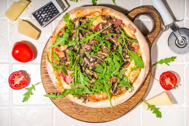 Pizza fatta in casa con funghi, pancetta, rucola e formaggio, su sfondo soleggiato estivo di piastrelle. le mani della ragazza nella foto tagliano e prendono una fetta di pizza vista dall'alto