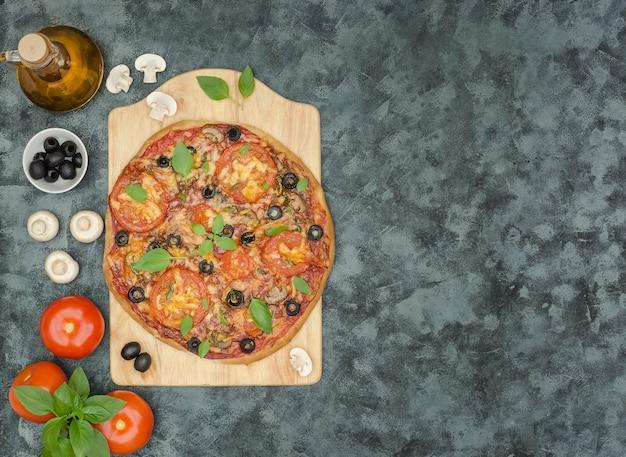 Pizza fatta in casa con funghi, olive e ingredienti su sfondo nero con copia spazio