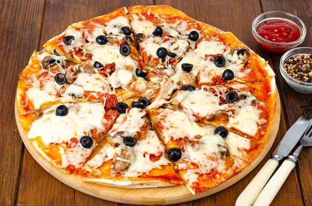 Pizza fatta in casa con peperoni, funghi, mozzarella e olive. foto di studio