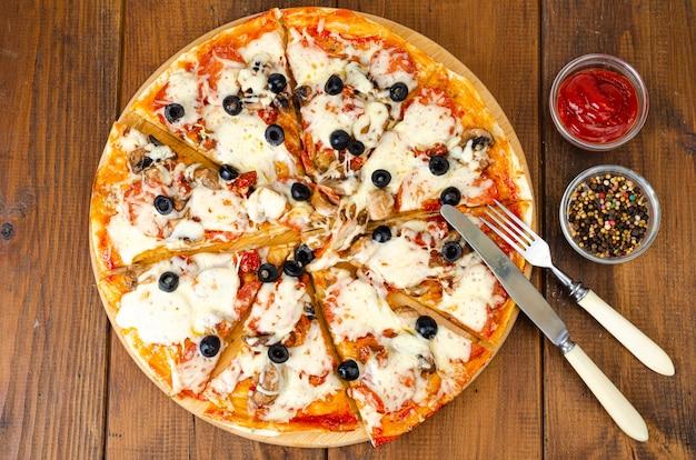 Pizza fatta in casa con peperoni, funghi, mozzarella e olive.