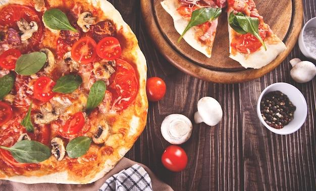 Pizza fatta in casa con salsiccia ai peperoni, pancetta decorata con spinaci e ingredienti sullo sfondo. vista dall'alto.