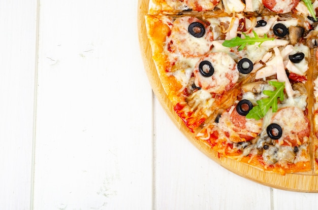 Pizza fatta in casa con salame, prosciutto e mozzarella sul tavolo di legno. foto di studio