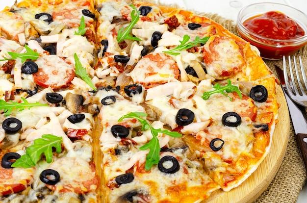 Pizza fatta in casa con salame, prosciutto e mozzarella sul tavolo di legno.