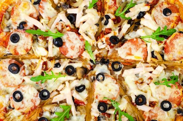 Pizza fatta in casa con salame, prosciutto e mozzarella sul tavolo di legno. Foto Premium