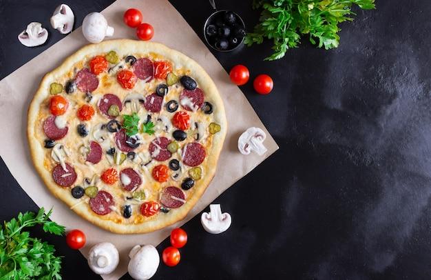 Pizza fatta in casa con salame, funghi e pomodorini su sfondo nero. spazio libero per il testo, vista dall'alto.