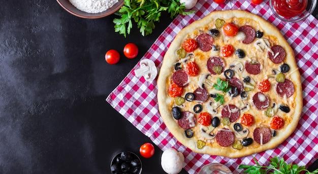 Pizza fatta in casa con salame, funghi e pomodorini su sfondo nero. un asciugamano rosso a scacchi. spazio libero per il testo, vista dall'alto.