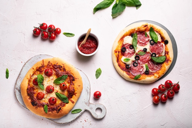 Pizza fatta in casa con pomodoro e basilico su una lavagna bianca