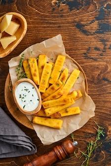Patatine fritte di polenta fatte in casa con sale marino, parmigiano, timo, rosmarino con salsa allo yogurt. polenta fritta tipica italiana. bastoncini di mais fritti. fondo in legno. vista dall'alto.