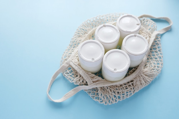 Vaso fatto in casa di yogurt greco in barattoli di vetro in un sacchetto di corda su uno sfondo azzurro. messa a fuoco selettiva, copia dello spazio.