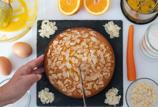 Preparazione casalinga della torta di carote con mandorle. torta di carote appena sfornata. tavolo con ingredienti e utensili da cucina utilizzati per realizzarlo