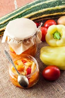 Conserve fatte in casa. insalata di zucchine e peperoni in un barattolo di vetro con ingredienti sullo sfondo