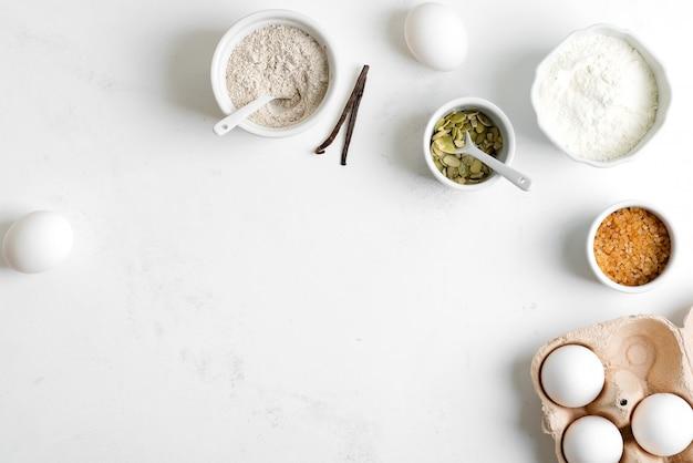 Produzione casalinga di pane fresco sano di altra pasticceria da ingredienti naturali su un tavolo grigio chiaro.