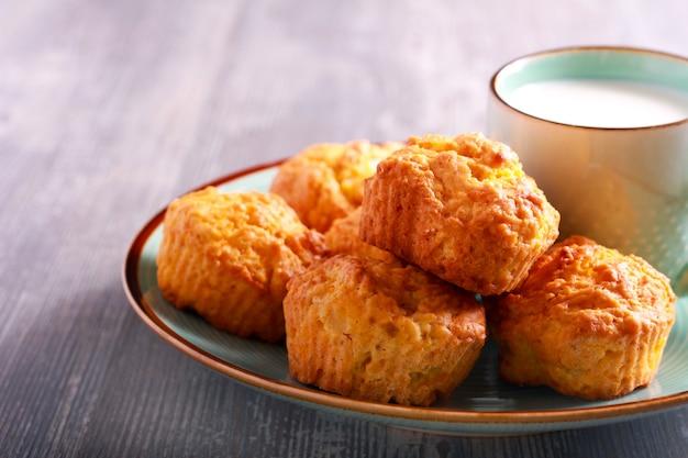 Muffin casalinghi della zucca sulla zolla e sulla tazza di latte