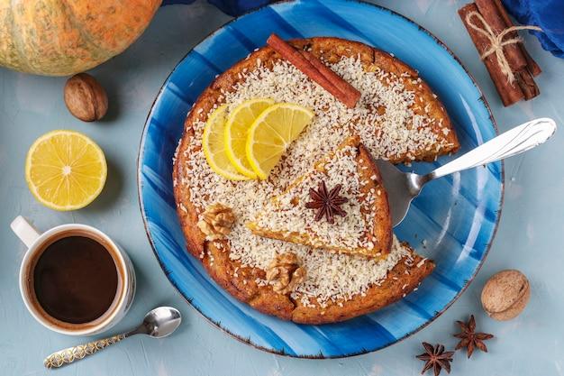 Torta di zucca fatta in casa con limone, cannella e noci, cosparsa di cocco, affettata, su una superficie blu chiaro, vista dall'alto