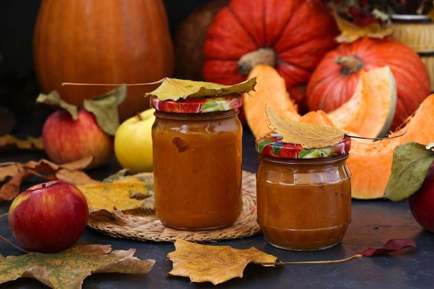 Purea di zucca fatta in casa e mele per bambini nelle banche su uno sfondo scuro. natura morta autunnale