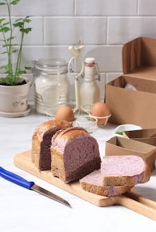 Pane viola fatto in casa a base di patate dolci viola giapponesi. con colore naturale. servito su tagliere in legno sfondo bianco con pacchetto di carta marrone e latte. concetto per una dieta sana bakery