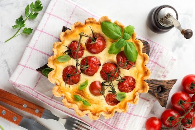 Torta di quiche fatta in casa con pomodorini, basilico, condimenti e formaggio su sfondo di pietra bianca. messa a fuoco selettiva