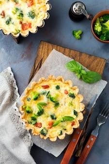 Torta quiche fatta in casa con salmone pesce rosso, broccoli, basilico, condimenti e formaggio su un tavolo di pietra grigia. messa a fuoco selettiva vista dall'alto.