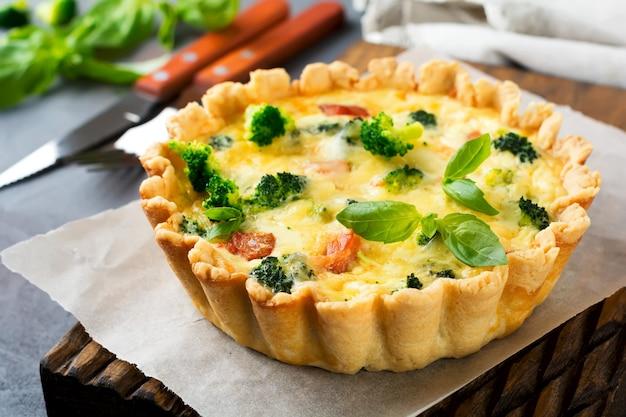Torta quiche fatta in casa con salmone pesce rosso, broccoli, basilico, condimenti e formaggio su un tavolo di pietra grigia. messa a fuoco selettiva.