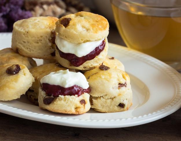 Focaccine di uva passa fatte in casa con marmellata di fragole fatta in casa, panna rappresa e tè.