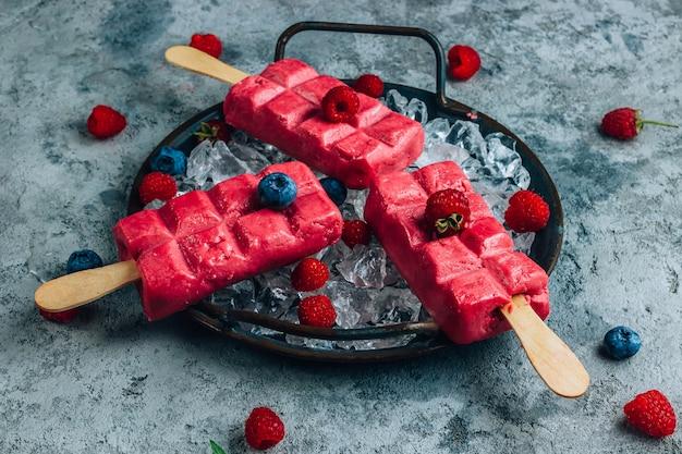 Ghiacciolo di gelato al lampone fatto in casa su un vassoio di metallo su sfondo di cemento con ghiaccio.