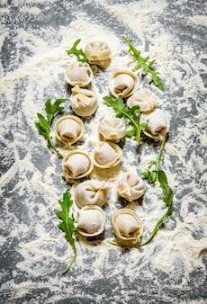 Ravioli fatti in casa ripieni di erbe aromatiche. sul tavolo di pietra con la farina. vista dall'alto