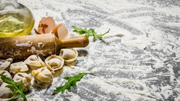 Ravioli fatti in casa con olio d'oliva e col mattarello. sul tavolo di pietra con la farina. spazio libero per il testo.