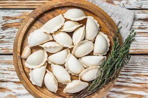 Gnocchi surgelati crudi fatti in casa, vareniki, pierogi ripieni di patate su una tavola di legno. fondo di legno bianco. vista dall'alto.