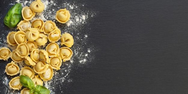 Tortellini italiani crudi fatti in casa e basilico su uno sfondo scuro
