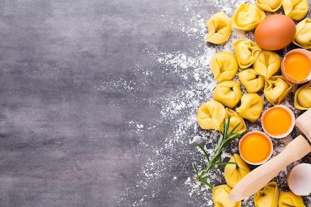 Tortellini italiani crudi fatti in casa e foglie di basilico.