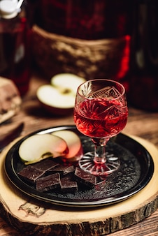 Ribes rosso fatto in casa nalivka e cioccolato con mela a fette su vassoio di metallo