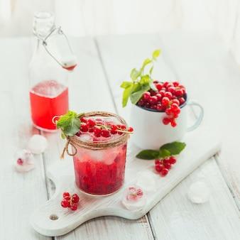 Cocktail di frutta rinfrescante fatto in casa o punch con champagne, ribes rosso, cubetti di ghiaccio e foglie di menta