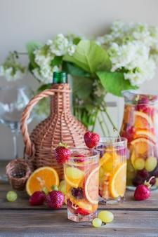 Sangria alla frutta rinfrescante fatta in casa o punch con champagne, fragole, arance e uva