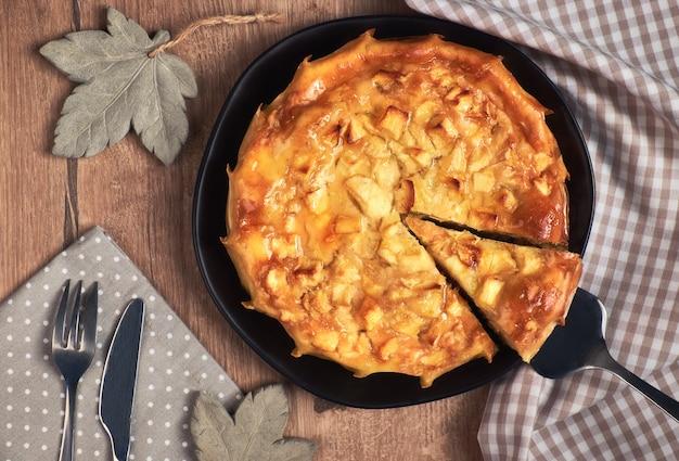 Torta di mele rotonda fatta in casa con una fetta tagliata su un piatto nero