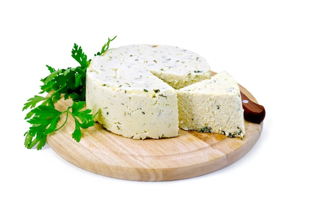 Formaggio rotondo fatto in casa con erbe e spezie, prezzemolo e coltello su una tavola di legno rotonda isolata su priorità bassa bianca