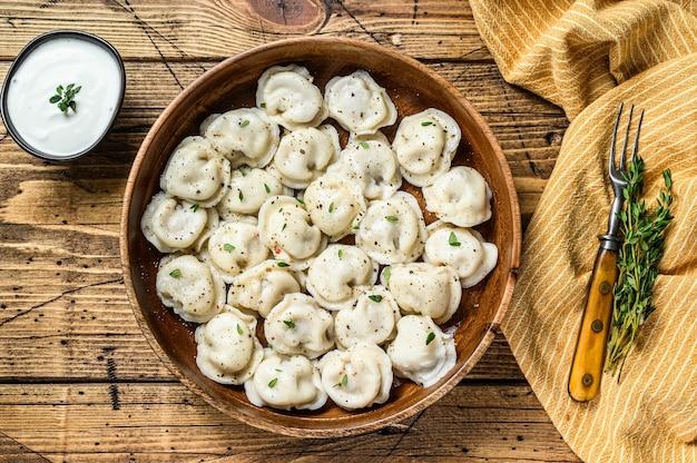 Gnocchi russi fatti in casa pelmeni con carne di manzo e maiale in una ciotola di legno