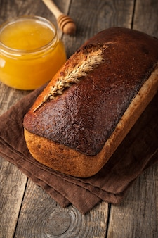 Pane di segale fatto in casa e vasetto di vetro miele sul tavolo di legno