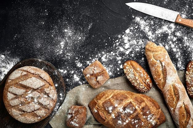 Pane di segale fatto in casa cosparso di farina e vari cereali e semi su sfondo nero con spik...