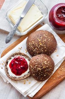 Panini di segale fatti in casa con semi di lino, sesamo e semi di papavero bianco serviti con burro e marmellata di jostaberry su tavola di legno