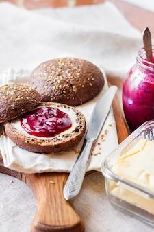 Panini di segale fatti in casa con semi di lino, sesamo e semi di papavero bianchi serviti con burro e marmellata di jostaberry